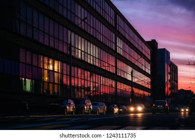 Glass building with reflected evening city and vibrant violet, orange and red sunset sky in it and cars on street, Minsk, Belarus
