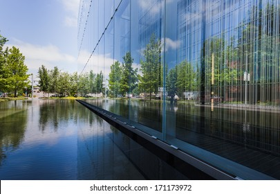A glass building reflecting its surroundings