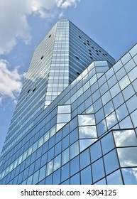 Glass building in Warsaw under blue sky with clouds