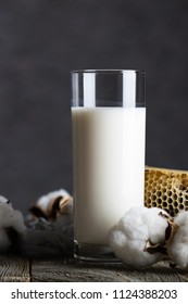 Glass of butter milk and cotton plant bolls. Honeycomb in the background. Closeup
