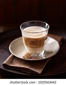 Glass of cafe latte. Brown rustic background.