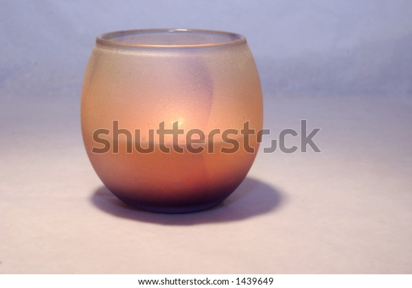 Glass candleholder lit with a peach candle. Contains clipping path.