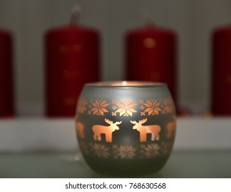 Glass candlestick with reindeers and snowflakes and with burning candle. Focus is on the reindeer.