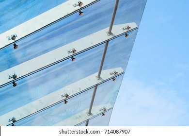 Glass Canopy Against Blue Sky Background. Fastening Elements of Glass Canopy on Modern Building
