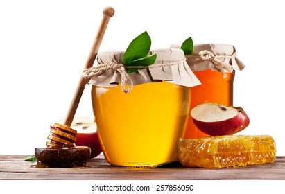 Glass cans full of honey, apples and honeycombs on wood. File contains clipping paths.