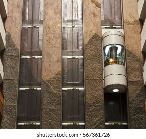 glass capsule elevator with people or tourist in the lift on vintage wall in the hall at luxury hotel or building