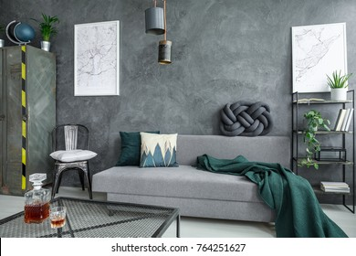 Glass carafe on table in grey living room with green blanket on couch and white pillow on chair