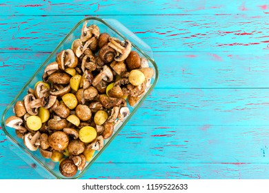 Glass casserole dish with diced baby bella mushrooms and potatoes ready to be roasted in the oven on a blue crackle paint wooden background with copy space