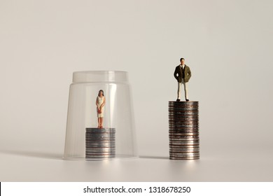 A glass ceiling concept. A miniature man and a miniature woman standing on a pile of coins of different heights.