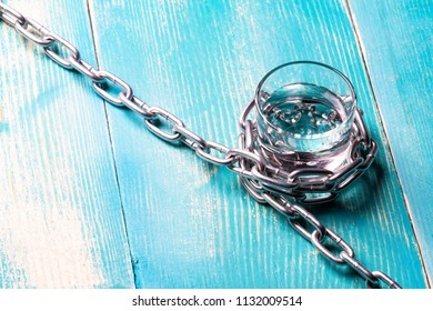 glass and chain of metal, restriction in alcohol, background blue tree