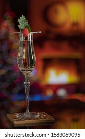 A glass of champagne in a cozy room with Christmas decorations and a lit fireplace.