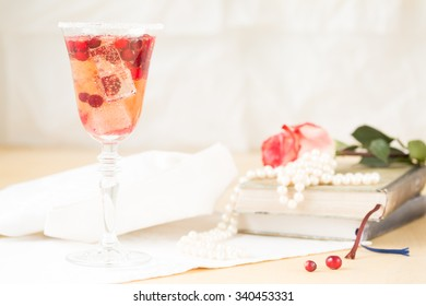 Glass of champagne and cranberry cocktail with vintage books and pearls. Lightweight background. Vintage style. Horizontal