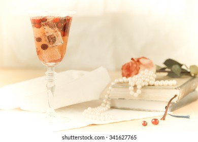 Glass of champagne and cranberry cocktail with vintage books and pearls. Lightweight background. Vintage style. Horizontal. Vintage tone and overlight vignetting