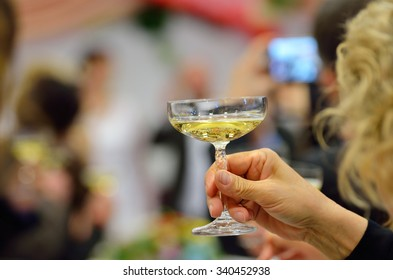 Glass of champagne in hand of girl during wedding dinner