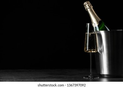 Glass of champagne near bucket with bottle on black background, space for text