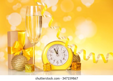 A glass of champagne next to the clock and Christmas gifts on a yellow background