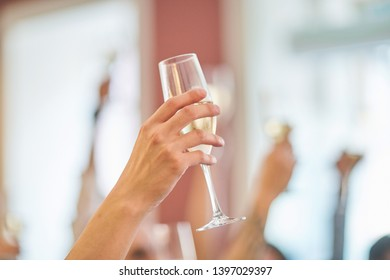 Glass of champagne on the background of friends at a party. - Shutterstock ID 1397029397