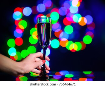 Glass of champagne on bright background with bokeh effect