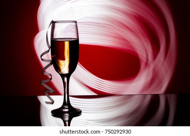 glass of champagne on  festive red background. party