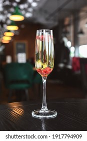 Glass of champagne with pomegranate seeds on table over blurred background. Restaurant or bar concept, romantic st. Valentines day celebration.