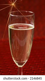 Glass of champagne and sparkle on red background