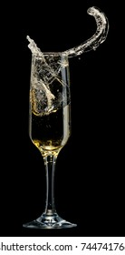 Glass of champagne with splashes on a black background