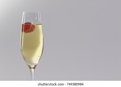 Glass of champagne with strawberry on grey background with copyspace..