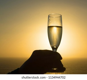 A glass of Champange at Sunset by the ocean.