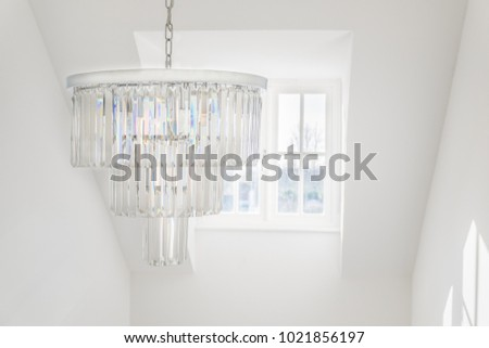 glass chandelier hanging infront of a dormer window in a bright white room