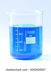 Glass chemical beaker with blue chemicals dissolved in water isolated on white background