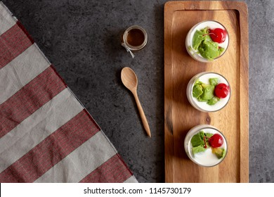 Glass of Cherry and avocado sliced in yogurt on wooden background.