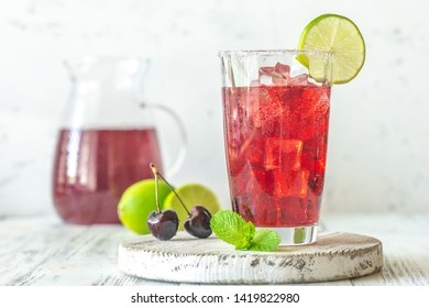 Glass of cherry mojito garnished with lime slice