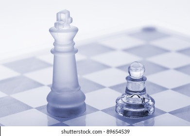 Glass chess. A pawn and a king. Blue toned. It is isolated on a white background.
