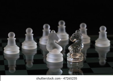 glass chess pieces on a black background