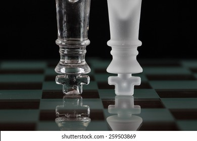 Glass chess pieces (the kings) up side down on a glass chess board with reflection.