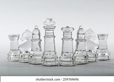Glass chess pieces in v-shape formation from king and queen.