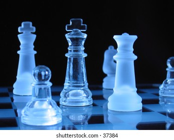 Glass chessmen during a play against dark background.