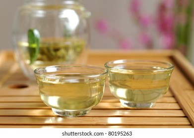Glass Chinese tea set on wooden board with green tea leaves