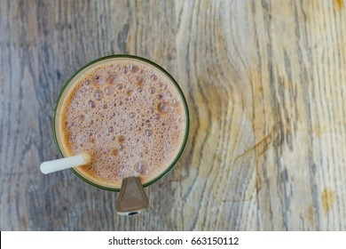 Glass of chocolate drink on wooden table.