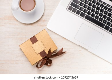 Glass of chocolate milk and variety chocolates  on table with gift box and laptop.