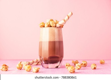 Glass of chocolate milkshake with caramel popcorn. Iced cocoa drink and waffle on pink background