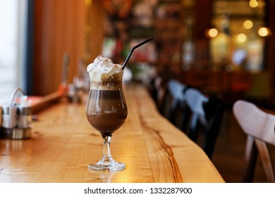 Glass of chocolate mocha with a cap of whipped cream and straw on a table in a cafe. Shallow focus and blurred background.