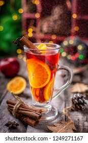 Glass of Christmas mulled red wine with spices and fruits surrounded by festive decoration,  on a wooden rustic table. Vertical composition