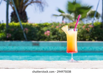 Glass of Cinderella kids cocktail on the pool nosing at the tropical resort. Horizontal
