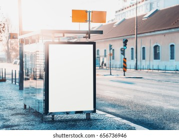 Glass city bus stop with mock-up of information poster, vertical blank billboard near road, empty white placeholder frame in urban settings with copy space for logo or advertising text on sunny day