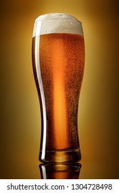 Glass of classic lager beer on gradient yellow to brown background. Studio shot.