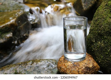 Glass of clean water against natural flowing water backgroubd