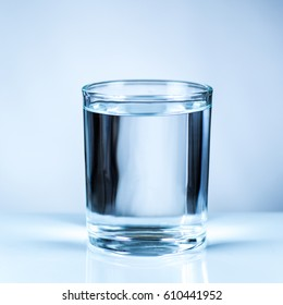 glass of clean water on blue background