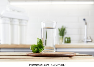 A glass of clean water with osmosis filter, green leaves on a wooden table in kitchen interior. Concept of a water treatment.