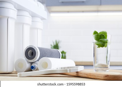 A glass of clean water with osmosis filter and cartridges on wooden table in a kitchen interior. Concept Household filtration system.